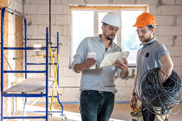 Two builder engineers talking at building site, engineer explaining a drawing to a worker