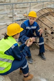 Два строителя болтают и обедают в перерыве