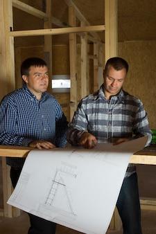 半分建設された木造家屋の中に立っている2人のビルダーが一緒に設計図をチェックします
