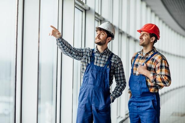 2人の建築業者が大きな窓のそばに立ち、仕事でたむろしています