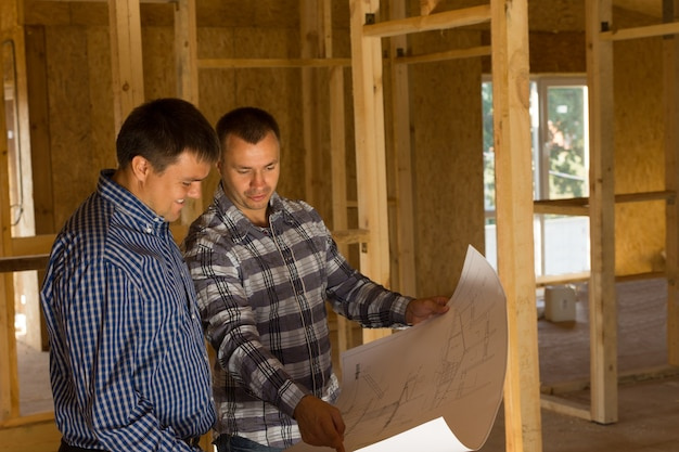 Two builders inside a half completed timber frame house standing having a discussion over a blueprint of the building