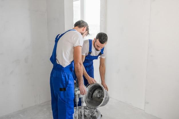 Два строителя замешивают цемент строительным миксером