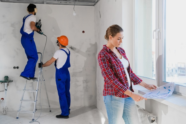 Two builders in overalls and soundproof headphones drill the wall. the flat owner examines the layout of the apartment