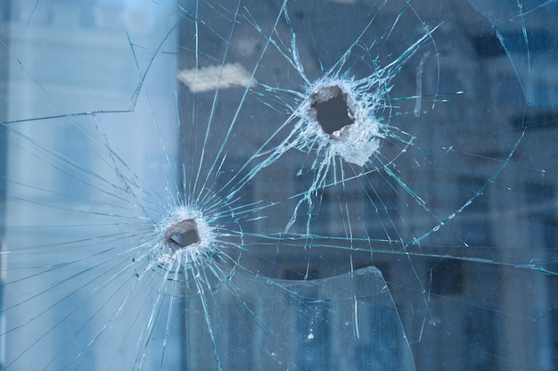Two bullet holes in the glass windows