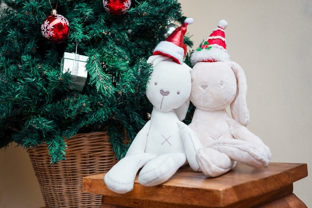 Two bunnies toy in the christmas santa cap near the christmas tree
