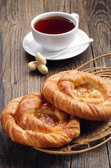 木製のテーブルにジャムとお茶のカップ2つのパン