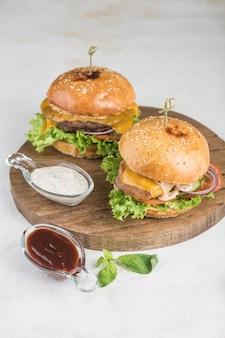 明るい背景の木製ボードに、鶏肉と牛肉の新鮮な野菜、ハーブ、ハンバーガーソース、ゴマパンを添えた2つのハンバーガー。テキストのコピースペースを含む上面図。ファストフード。