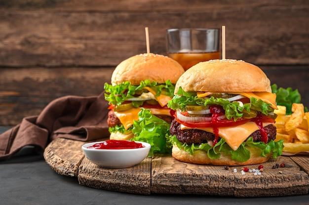 고기, 야채, 치즈, 감자튀김, 콜라를 나무 배경에 넣은 두 개의 버거. 측면 보기, 복사 공간입니다.