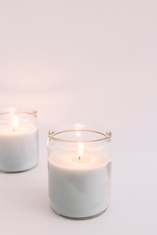 Two burning candles in glass candlesticks