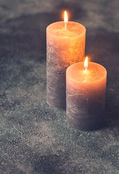Two burning candles on gray