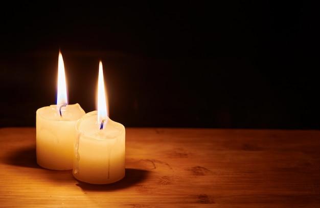 어두운 밤에 테이블에 두 개의 불타는 촛불. 희망과 기억의 불꽃. 복사 공간이 있는 보기를 닫습니다.