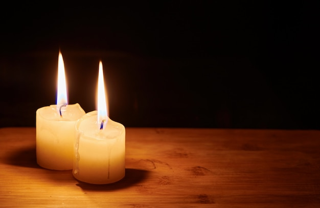 Two burning candles on the table in night dark. flame of the hope and memory. close up view with copy space.