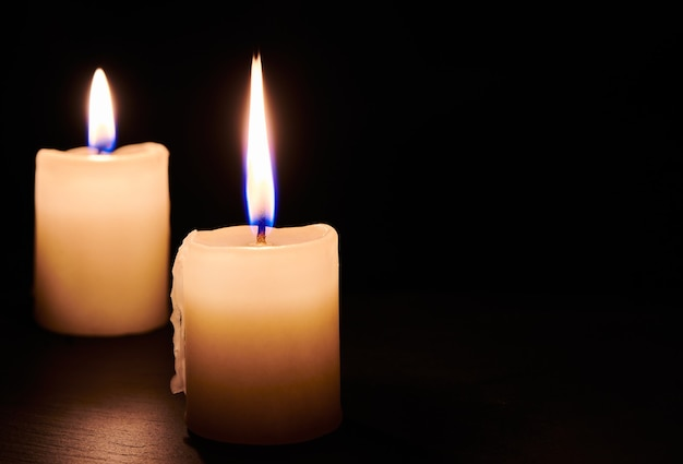Two burning candles on the table in night dark