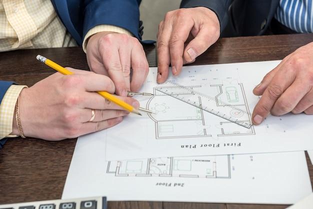 オフィスの机で家の建築計画に取り組んでいる2人のbusimessman。青写真に関するチームワーク