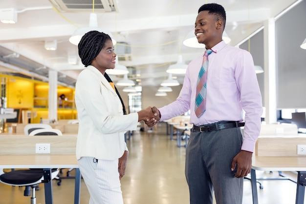 クラスが始まる前に、2人のビジネス黒人学生のネットワークハンドシェイクが成功する