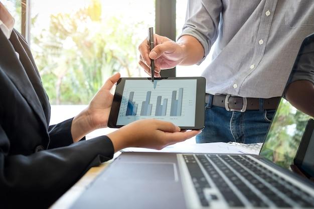 オフィスで職場でタブレットでグラフを提示し指している2つのビジネスの同僚