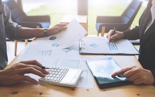 현대 사무실에서 주식 시장의 데이터 reseach에 대해 논의하는 두 비즈니스 동료