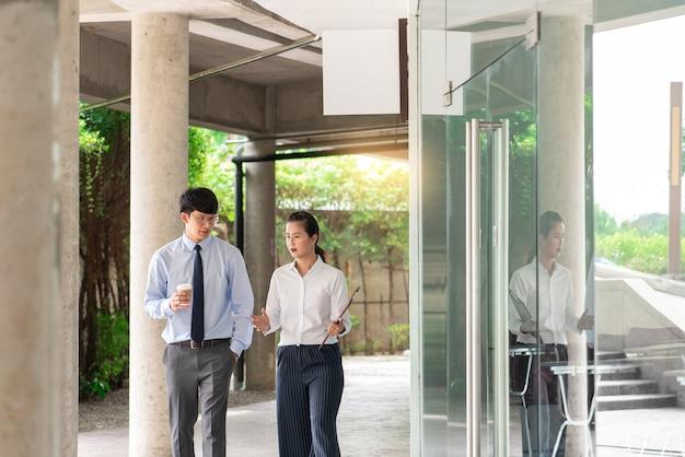 都会の環境でオフィスの外で新しいプロジェクトのビジネス会議について話し合う2人のビジネス同僚。
