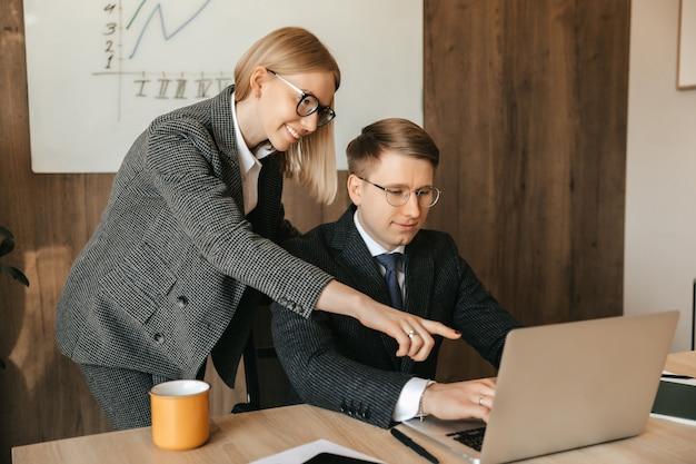 2人の同僚がドキュメントを見てラップトップで作業し、秘書または女性マネージャーがドキュメントを読み、実業家を笑顔にします。