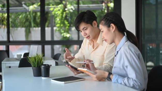 두 비즈니스 컨설팅 또는 사무실 직장에서 디지털 태블릿과 이야기.