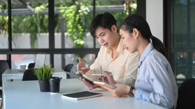 Two business consulting or talking with digital tablet on office workplace.
