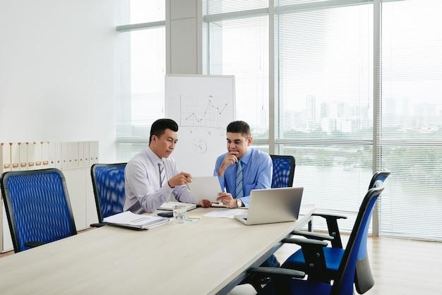 Два руководителя бизнеса обсуждают контракт в конференц-зале