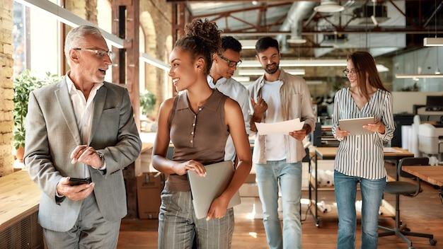 オフィスの廊下を同僚と歩きながら何かについて話し合う2人のビジネス専門家