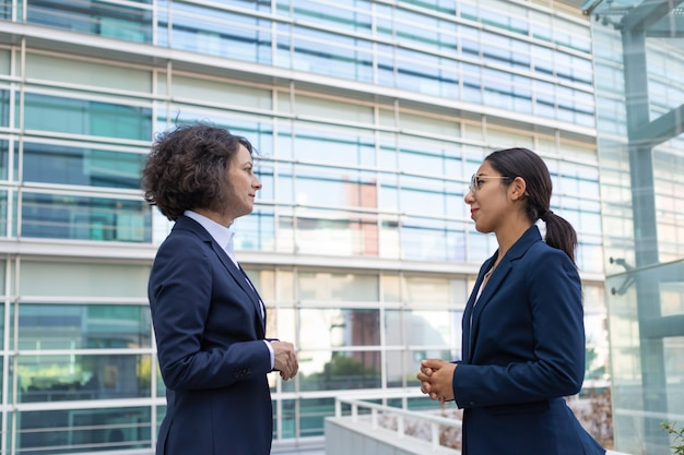 Two business ladies discussing project near office