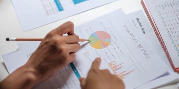 Два бизнес-лидера обсуждают диаграммы и графики, показывающие результаты, планируют начать новую стратегию для большого успеха