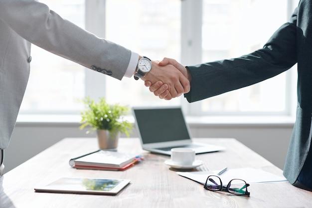 협상 및 재정 서류에 서명 한 후 책상 위에 악수하는 formalwear의 두 비즈니스 리더