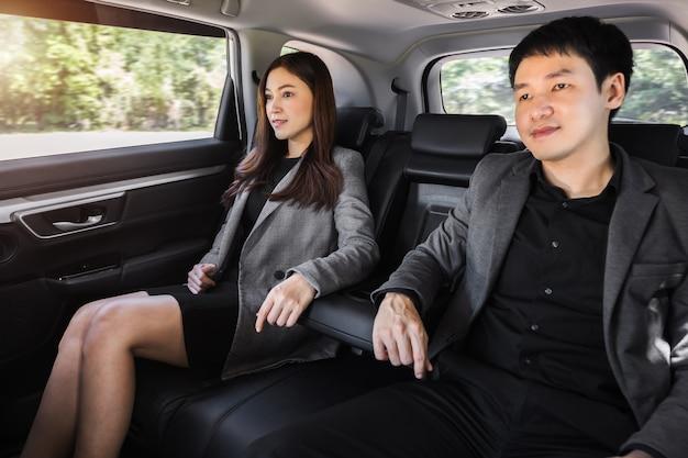 車の後部座席に座っている2人のビジネスの男性と女性