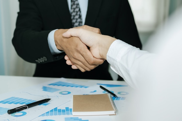Two business man investor handshake deal with partner after finishing up business meeting