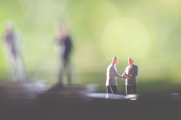 Two business man,saving and finance concepts. miniature people stand