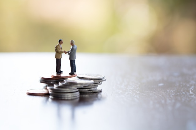 Two business man,saving,investment and finance concepts. miniature people stand