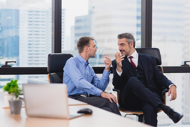 Two business man sitting near window working and discuss after success to agreement in creative office meeting room