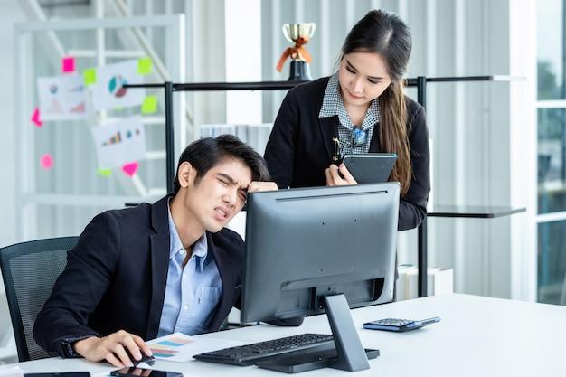 Два деловых человека подчеркнуты на работе. деловые партнеры помогают давать положительные рекомендации, работая с компьютером на деревянном столе, и идеи на встрече в офисе.
