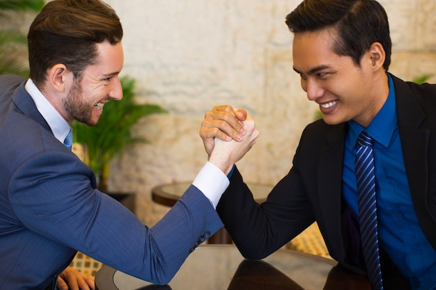 Two business men arm wrestling stubbornly in lobby