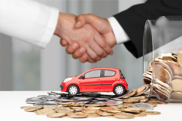 Two business men handshaking with car and money coins. deal concept