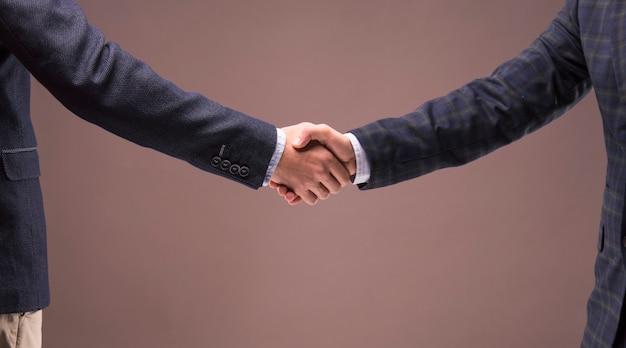 Двое деловых людей в костюмах пожимают друг другу руки