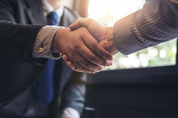 Two business men shaking hands during a meeting to sign agreement and become a business pa
