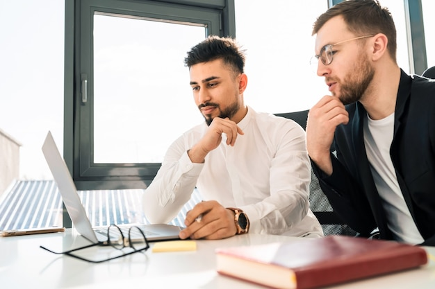 Two business men thinks about project at laptop