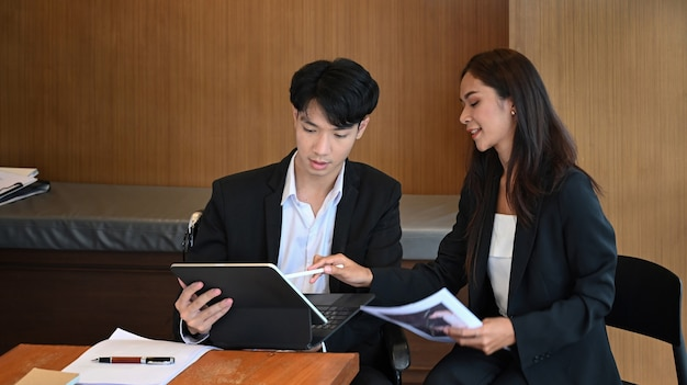 Two business office workers working on project together in office.
