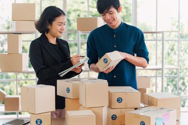 2人の事業主。顧客に配達するために製品の小包ボックスをチェックします。オンライン販売のコンセプト