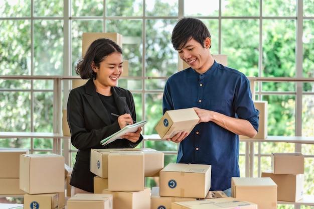 Два владельца бизнеса. проверка посылочной коробки продукта для доставки покупателю. концепция онлайн-продаж