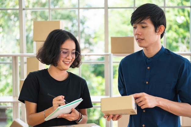 Two business owner. checking parcel box of product for deliver to customer.