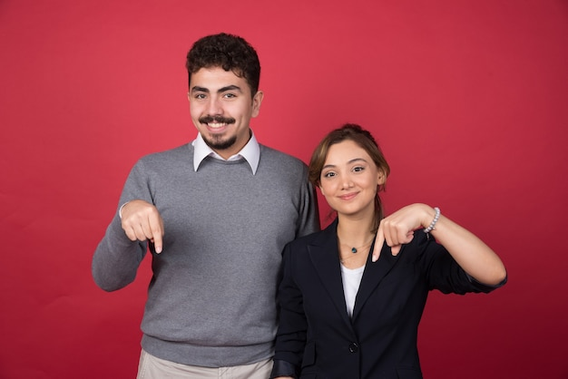 Два деловых партнера, указывая на нижнюю сторону на красной стене