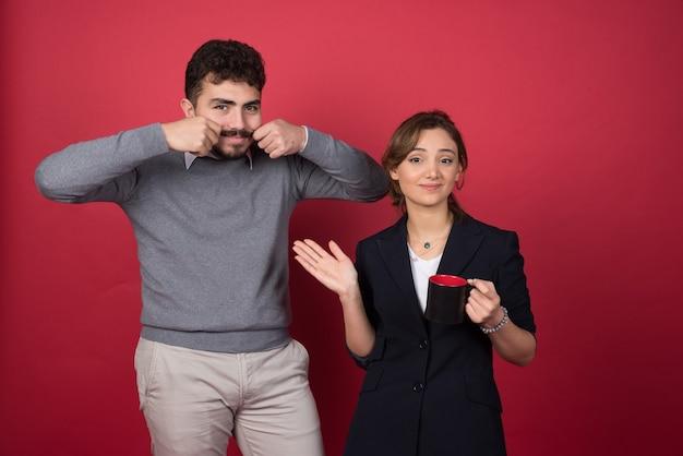 행복 하 게 붉은 벽에 서있는 두 비즈니스 파트너