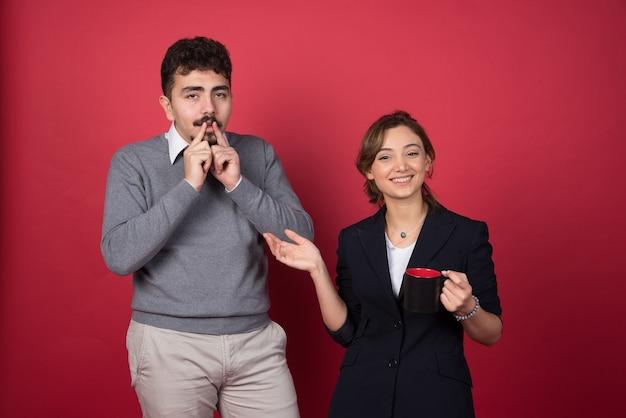 Due soci d'affari felicemente in piedi sulla parete rossa