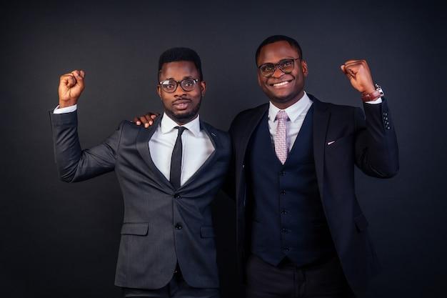 Два деловых партнера обнимаются в студии на черном фоне.