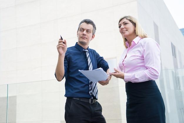 Два деловых партнеров, глядя на соседнее здание на открытом воздухе.